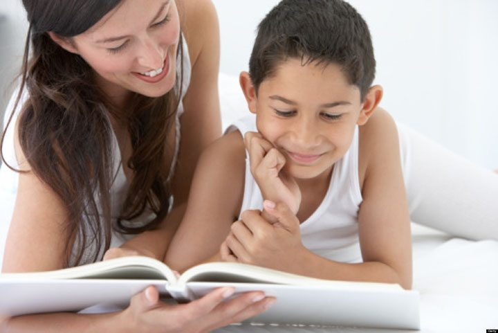 Mother and son (8-10) reading book, smiling
